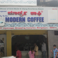 People drinking coffee at outdoor market coffee shop