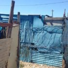Blue shanty house with barbed wire
