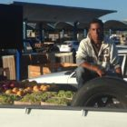 Fruit seller sitting in truck at outdoor public food market