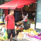 Man with child in stroller shopping at outdoor fruit stand