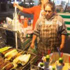 Man roasting corn at outdoor stand