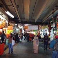 People walking through market looking at vendors