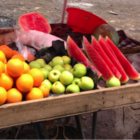 watermelon, applies and oranges on outdoor table