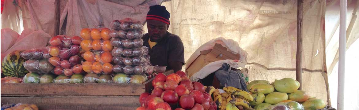 Man at market stall with fruit